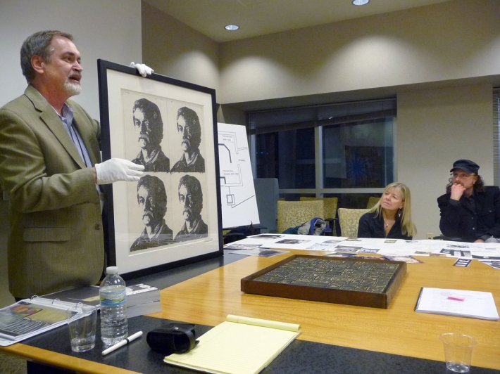 Curator Mark Ruschman shows a self portrait of Jim that will be used for the exhibition